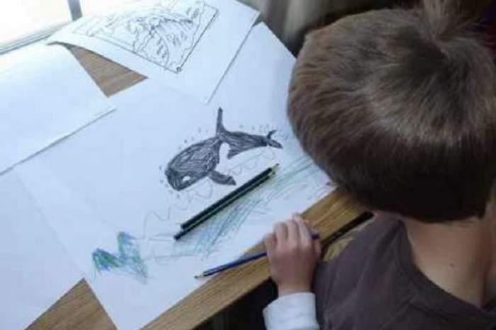 Un copil care desenează balena albastră