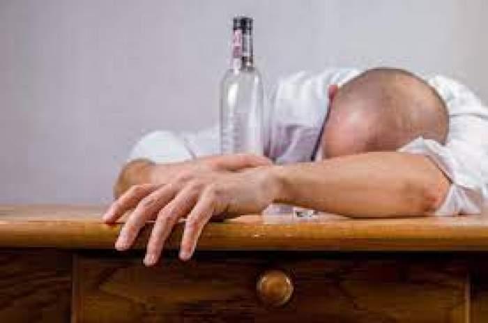 Un bărbat cu capul pe masă și o sticlă goală lângă