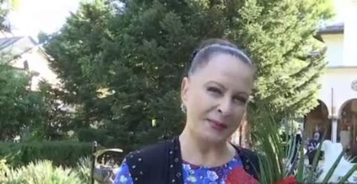 Maria Dragomiroiu , cu flori în brațe, zâmbitoare