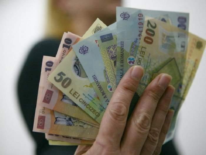 O persoană care ține în mână mai multe bancnote