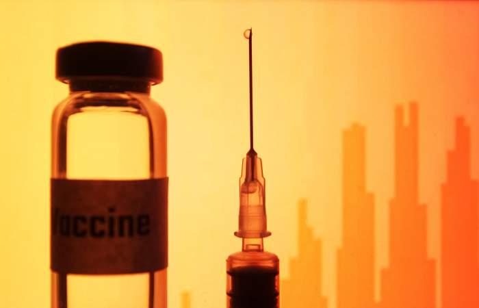 O seringă și o sticlă de vaccin pe un fond portocaliu