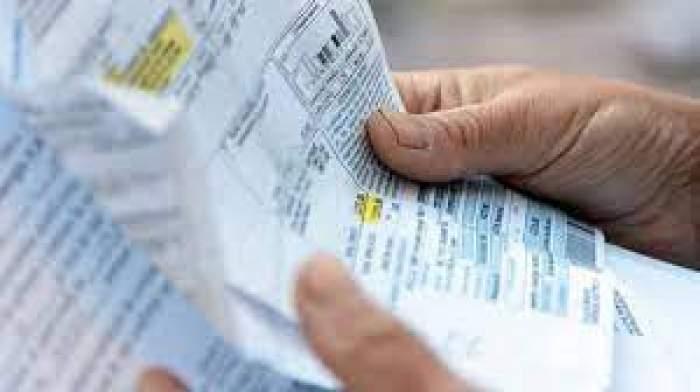 Un om care ține o factură la curent în mână