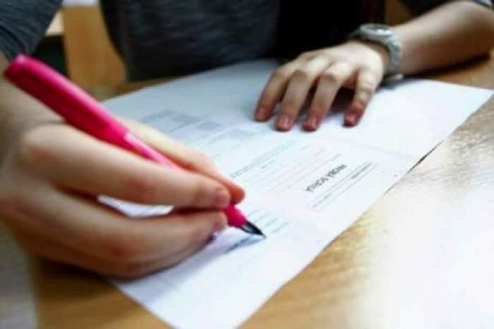 un elev care scrie la examen
