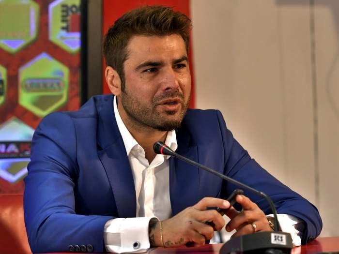 Adrian Mutu, în costum albastru, la o conferință